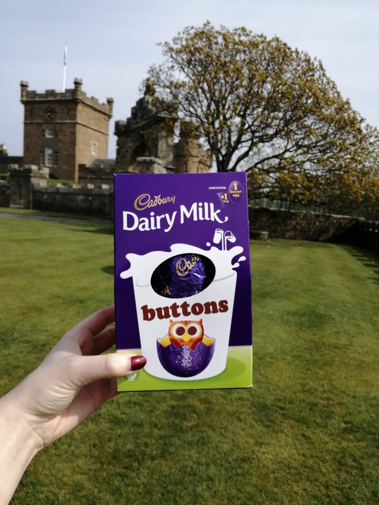 Picture of my hand holding up a Dairy Milk Easter egg in front of Culzean Castle Country Park